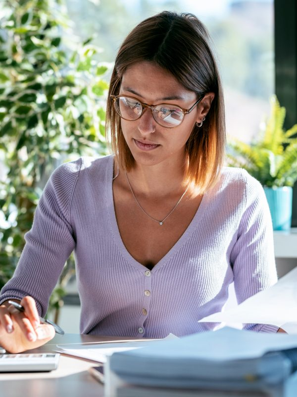 Shot of concentrated young business woman working with calculator while consulting some documents in the office at home.